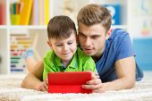 dad and son kid play with tablet computer indoors