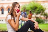 Woman eating an apple outdoors