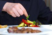 Handsome chef dressed in black uniform decorating tasty food in restaurant