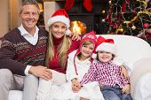 Portrait of a smiling family sitting on sofa at christmas time at home in the living room