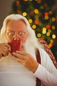 Father christmas drinking hot drink at home in the living room