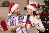 Happy couple in santa hat holding present at home in the living room
