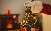Hand of santa holding car key at home in the living room