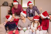 Happy extended family in santa hat holding gifts at home in the living room