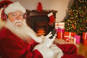 Smiling santa listening music with his smartphone at home in the living room