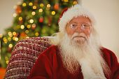 Portrait of santa claus with his glasses at home in the living room