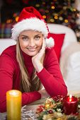 Happy blonde woman in santa hat at home in the living room