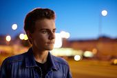 stock photo of boys night out  - Closeup of a teenage boy in an urban environment at night - JPG
