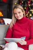 Festive blonde woman using her credit card and tablet pc at home in the living room
