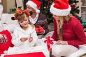 Daughter opening christmas gift with mother at home in the living room