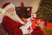 Smiling santa claus holding gift at home in the living room