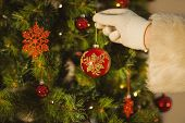 Hand of santa hanging a bauble on christmas tree at home