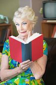 image of tawdry  - Uneasy single senior woman in green reading a book - JPG