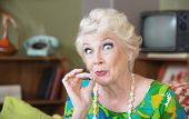 foto of excite  - Excited Caucasian senior woman in green smoking marijuana - JPG