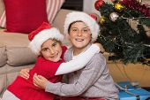 Smiling brother and sister hugging near the christmas tree at home in the living room