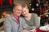 Portrait of smiling mature couple at table at home in the living room