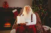 Santa claus showing his book at home in the living room