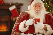 Smiling santa claus holding a mug at home in the living room