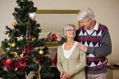 Senior couple decorating their christmas tree at home in the living room