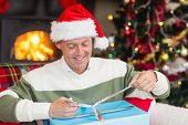 Smiling man in santa hat opening a gift at home in the living room