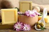 Handmade soap with the branches of rosemary on sackcloth, fresh flowers, olives on wooden background