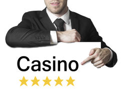 picture of poker machine  - businessman in black suit pointing on sign casino star rating - JPG