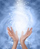 picture of ethereal  - Female hands reaching upwards into an ethereal blue and white colored swirling vortex energy field with a rain of glittering sparkles raining down - JPG