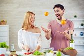 picture of juggling  - Happy young woman cooking salad in the kitchen - JPG