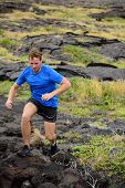 picture of volcanic  - Active man trail running on volcanic rocks in mountain background - JPG