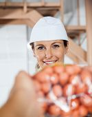 stock photo of slaughterhouse  - Portrait of happy female butcher selling packed sausages to customer in butchery - JPG