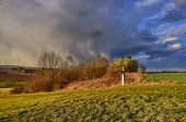 stock photo of calvary  - April evening in spring landscape with dramatic sky and calvary - JPG