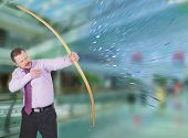 foto of archery  - Businessman practicing archery and modern interior in background - JPG