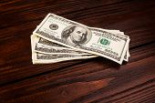 foto of american money  - Wooden table with money american hundred dollar bills - JPG