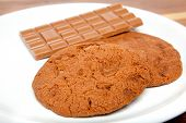 picture of chocolate-chip  - fresh chocolate cookie with chocolate chips on white plate - JPG