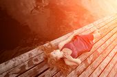 stock photo of glow  - Girl lying on the wooden floor in the sunlight - JPG