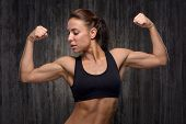 picture of bicep  - Young mixed race sporty woman wearing black tracksuit for training - JPG