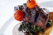 stock photo of chateaubriand  - Chateaubriand steak served with grilled tomatoes on top of the cooked spinach shot with deep depth of field - JPG
