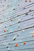 stock photo of climbing wall  - Grunge surface of an artificial rock climbing wall with toe and hand hold studs - JPG