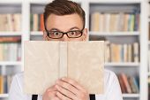 stock photo of nerd glasses  - Surprised young nerd man in glasses looking out of the book while standing at the library - JPG