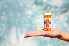 stock photo of mary jane  - An unidentifiable womans hand holds Medical Marijuana aka Pot - JPG