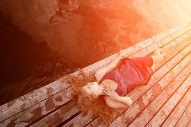 pic of glow  - Girl lying on the wooden floor in the sunlight - JPG