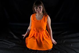 picture of curvy  - Image of curvy woman in orange dress on black background - JPG