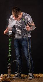 picture of hookah  - Tattooed man smoking traditional hookah - JPG