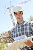 Construction worker with electronic tablet and plan