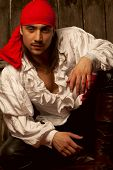 Sexy guy dressed as pirate against wooden background