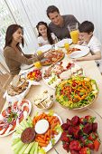 An attractive happy, smiling family of mother, father, son and daughter eating salad and pizza at a