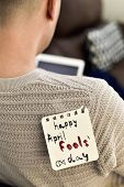 closeup of a young caucasian man seen from behind using his tablet, with a note with the text happy  poster