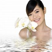 Beautiful woman with flower in water