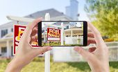 Female Hands Holding Smart Phone Displaying Photo of Sold For Sale Real Estate Sign and House Behind poster