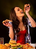 Woman eating pizza and hamburger. Student consume fast food. Girl opened her mouth to take bite of s poster